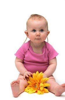 baby with hearing aid and flower