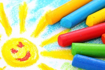 drawing of a sun with with a smily face and blue sky and green grass with various colors of crayons next to it