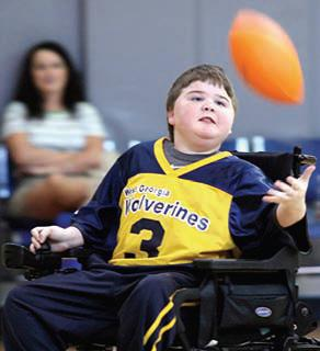 Young football player in motorized wheelchair