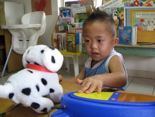Boy using a simple switch to operate toy dog with a high chair and books in the background