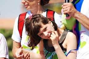 Young Girl displaying Rett Syndrome features looks at the camera while standing by adults