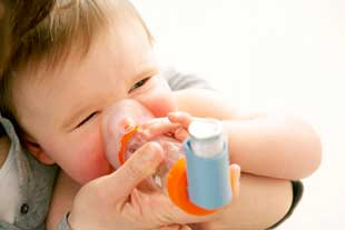 A baby using a spacer with an inhaler. The spacer acts as a reservoir, retaining the vapour from the inhaler and allowing the patient to inhale it at their chosen rate.